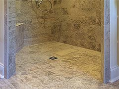 This barrier-free shower stall showcases custom tile work and the seamless floor is designed to quickly draw water to the drain without the need for a barrier or curb