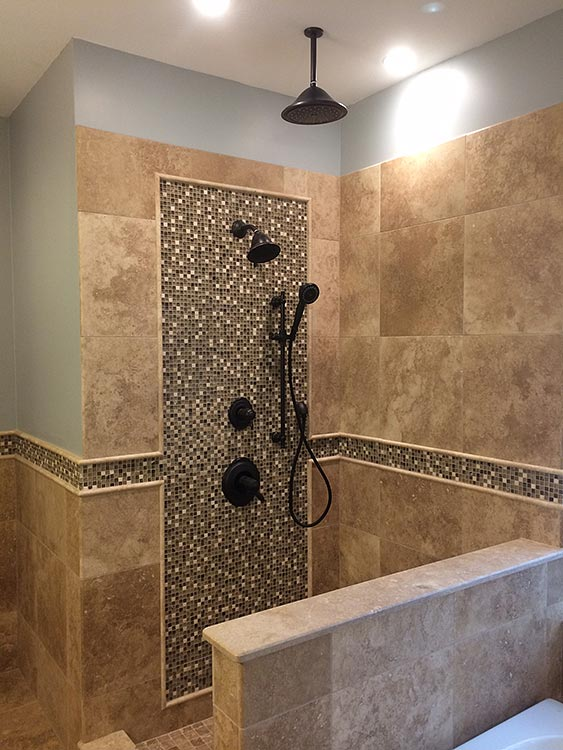 this custom travertine shower features a raincan shower head and