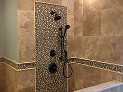This custom Travertine shower features a Raincan shower head and intricate custom tile work